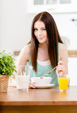 Girl eating healthy muesli and citrus juice. Portrait of the girl eating healthy muesli with milk and orange juice sitting at the kitchen table Stock Images