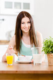 Girl eating healthy muesli and orange juice Stock Images