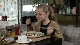 Girl is eating her dinner. In cafe stock video