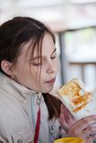 Girl eating a hot dog in a cafe. Royalty Free Stock Photography