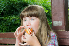Girl eating a hot dog. Little girl eating a hot dog on a bench in the summer outdoors Royalty Free Stock Image