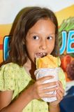 Girl eating hot dog. Portrait of a cute little girl eating hot dog Royalty Free Stock Photography