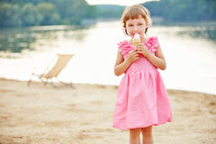 Girl eating ice cream cone in summer Stock Images