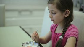 Girl eating ice cream in the kitchen stock footage