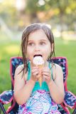 Girl eating ice cream outside stock image