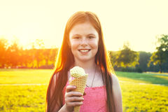 Girl eating ice cream in sunset light. Redhead girl with freckles eating ice cream in sunset light Royalty Free Stock Images