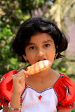 Girl eating ice lolly Royalty Free Stock Images