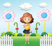 A girl eating an icecream near the fence with giant candies Royalty Free Stock Photography