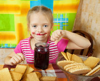 Girl eating jam from  jar Stock Photos