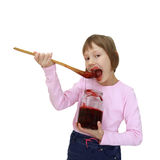 Girl eating jam from the jar Stock Photography