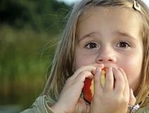Girl eating juicy apple Royalty Free Stock Image