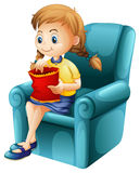 A girl eating junkfoods while sitting down Stock Image
