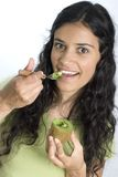 Girl eating kiwi Stock Images