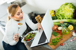 Girl eating with laptop in kitchen Stock Photography