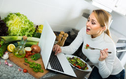 Girl eating with laptop in kitchen Royalty Free Stock Photography