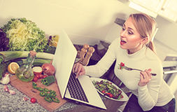 Girl eating with laptop in kitchen Stock Photos