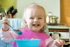 Girl eating. Little girl eating in the kitchen royalty free stock image