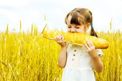 Girl eating a long loaf Stock Image