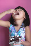 Girl eating marshmallow Stock Images