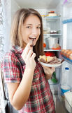 Girl eating  meat from  fridge Stock Photos