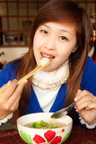 Girl Eating Meatball With Shopstick And Spoon Stock Images