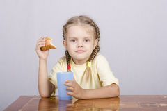 Girl eating a muffin with juice at the table Stock Photo