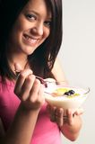 Girl eating natural yogurt. Young woman eating a bowl of natural yogurt.and fresh fruit of orange, pineapple, melon and blueberries Royalty Free Stock Photos