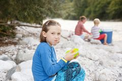 Girl eating in nature, having picnic with her family. Outdoor lifestyle, positive parenting, childhood experience concept. Girl eating in nature, having picnic royalty free stock image