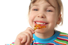 Girl eating orange lollipop, looking at camera Stock Images