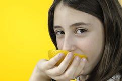 Girl eating orange over orange background. Royalty Free Stock Image