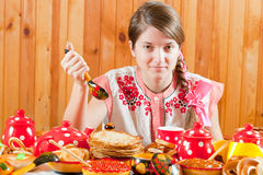 Girl  eating pancake with caviare. Girl in traditional  clothes eating pancake with caviare during  Shrovetide Stock Photo