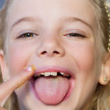 Girl eating peanut butter. Close up of a little girl eating peanut butter royalty free stock photo