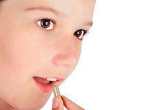 Girl eating a pill closeup Royalty Free Stock Photography