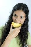 Girl eating pineapple Stock Photo