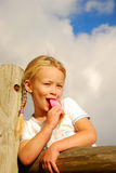 Girl eating pink ice-cream Stock Photography