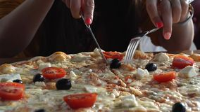 A girl is eating pizza in a cafe. Pizza in cafe. Close up view. Top view stock footage