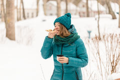 Girl eating pizza in the cold winter Royalty Free Stock Photo