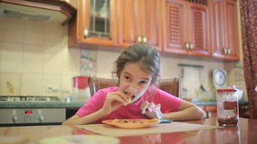 Girl eating pizza and fruit playing with phone in kitchen at table stock footage
