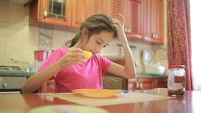 Girl eating pizza and fruit playing with phone in kitchen at table stock video