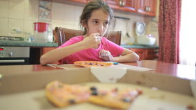 Girl eating pizza and fruit playing with phone in kitchen at table stock video footage