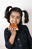 Girl eating pizza slice. And smiling royalty free stock photo