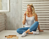 Girl eating pizza slice. Young attractive woman eating a piece of delicious pizza. She a T-shirt, jeans and sneakers sitting on the floor at home. Food delivery stock photo