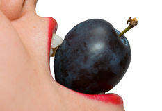 Girl eating a plum closeup Royalty Free Stock Images