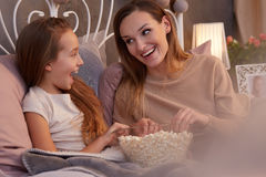 Girl eating popcorn in bed Stock Photography