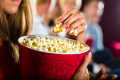 Girl eating popcorn in cinema or movie theater. Woman eating large container of popcorn in cinema or movie theater