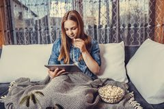 Girl eating popcorn and using digital tablet royalty free stock photo