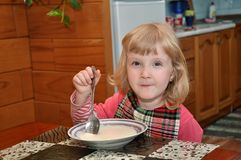 Girl is eating porridge Royalty Free Stock Image