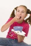 Girl eating porridge II. The nice girl-teenager eating porridge on lunch Royalty Free Stock Images