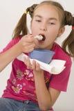 Girl eating porridge III. The nice girl-teenager eating porridge on lunch Royalty Free Stock Photo
