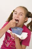 Girl eating porridge IV Stock Images